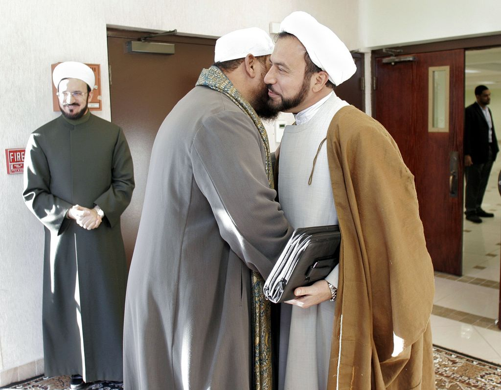 DEARBORN HEIGHTS, MI - JANUARY 10: Imam Husham Al-Husainy (R) greets a fellow Imam while Imam Mohammed Ali Elahi (L) of the Islamic House of Wisdom awaits the arrival of other Detroit area Imams at the Islamic House of Wisdom January 10, 2007 in Dearborn Heights, Michigan. Shi'ite and Sunni Imams from the metro Detroit area met at the mosque to discuss a way to reduce tensions and possible sectarian violence between the two communities that has occured following the celebration in the streets by local shi'ites and others of the execution of former Iraqi president Saddam Hussein. The need for discussion came after several business and mosques run by Shi'ite Muslims were vandalized. (Photo by Bill Pugliano/Getty Images)
